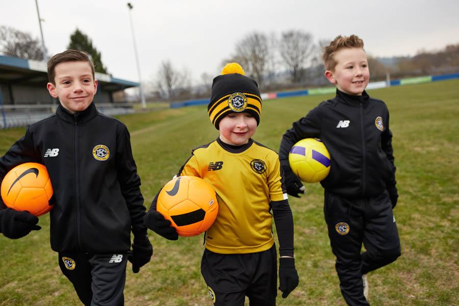Kids holding footballs at PSC class in Bradford