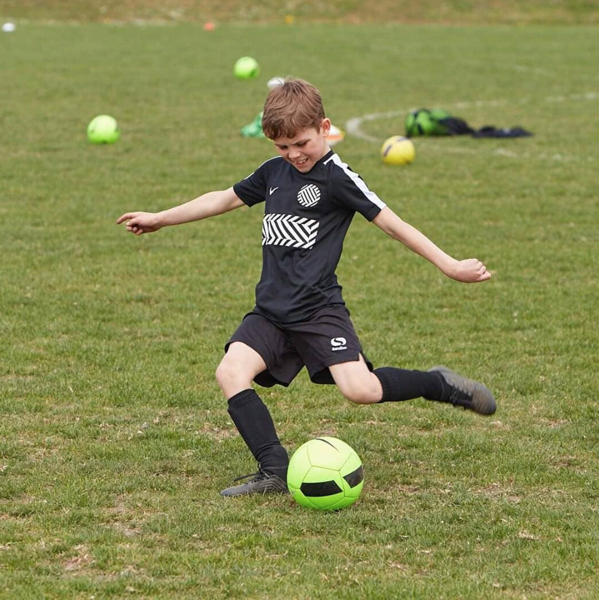 Boy Kicking Football During PSC Football Training For Kids